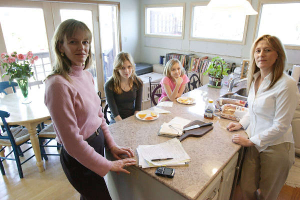 Marcy Greer, left, a partner with Fulbright & Jaworski's Austin office, is a member of a women's working group at the firm that examines issues that affect female employees. In her Austin home are daughters Jennings Greer, 14, Julia Greer, 9, and caregiver Bonnie Carrafa.