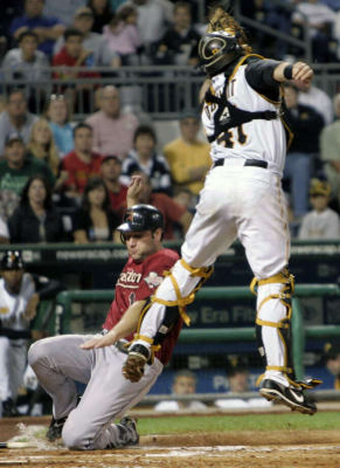 Pittsburgh Pirates catcher Ryan Doumit, top, leaps for a bad throw from left fielder Nyjer Morgan as Astros first baseman Lance Berkman, bottom, scores in the fourth inning on Friday at PNC Park in Pittsburgh. Photo: Keith Srakocic, AP