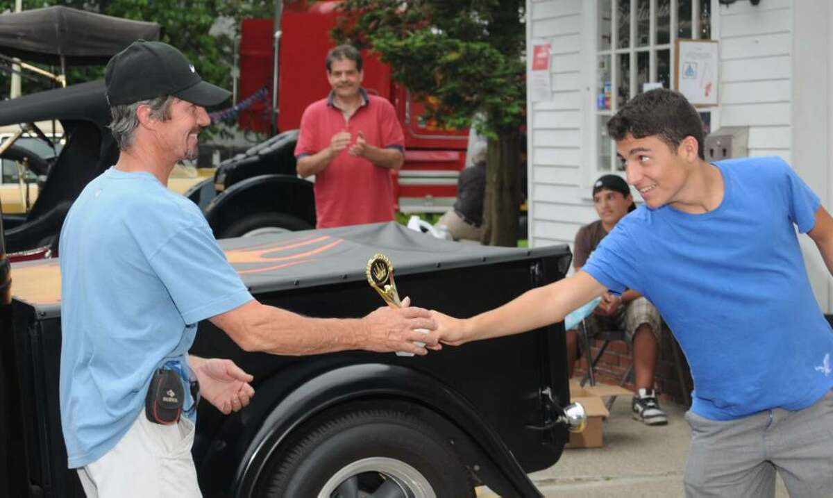 The Dodgingtown Market's annual car show was held Sunday in Newtown. Proceeds from the show, and profits from the market during the show, are donated to U.S. soldiers serving abroad and to breast cancer research. Teddy Hamilakis, 14, son of Dodgingtown Market owner, George Hamilakis, presents the tropy for 2009 Overall Best in Show to David Colby of Danbury, for his Factory 5, replica 1965 MK3 Roadster.