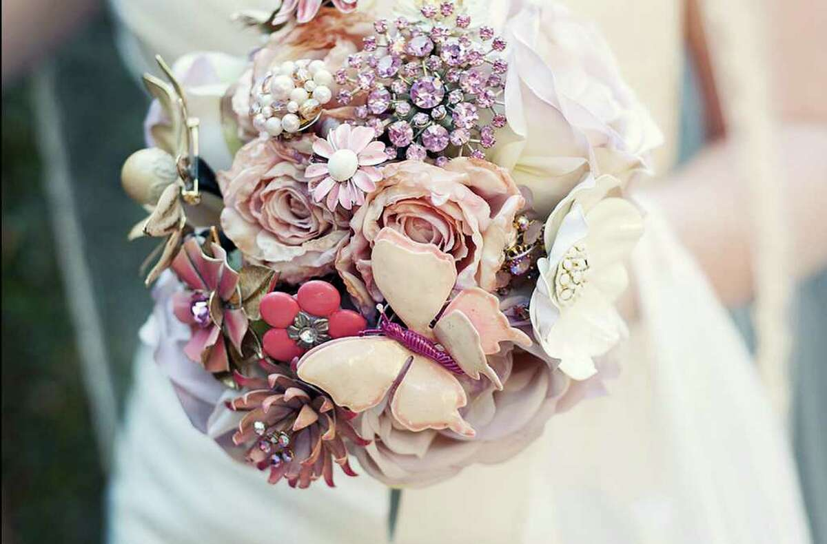 This undated photo courtesy of Liv Collins Photography shows a brooch bouquet designed by Jen Rose Diehl of Columbus, Ohio. Diehl creates bouquets out of vintage brooches. Each bouquet requires a lot of brooches. They need to overlap so the foam ball underneath doesn't show. Diehl wires each brooch and sticks the wires all the way through the ball. The wires become the bouquet's stems. (AP Photo/Liv Collins Photography)