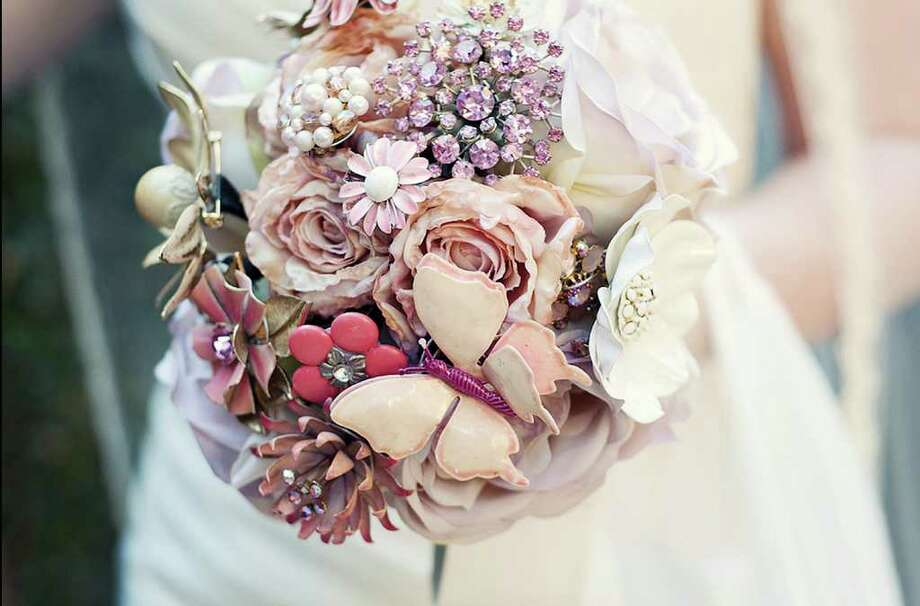 This undated photo courtesy of Liv Collins Photography shows a brooch bouquet designed by Jen Rose Diehl of Columbus, Ohio. Diehl creates bouquets out of vintage brooches. Each bouquet requires a lot of brooches. They need to overlap so the foam ball underneath doesn't show. Diehl wires each brooch and sticks the wires all the way through the ball. The wires become the bouquet's stems. (AP Photo/Liv Collins Photography) Photo: AP