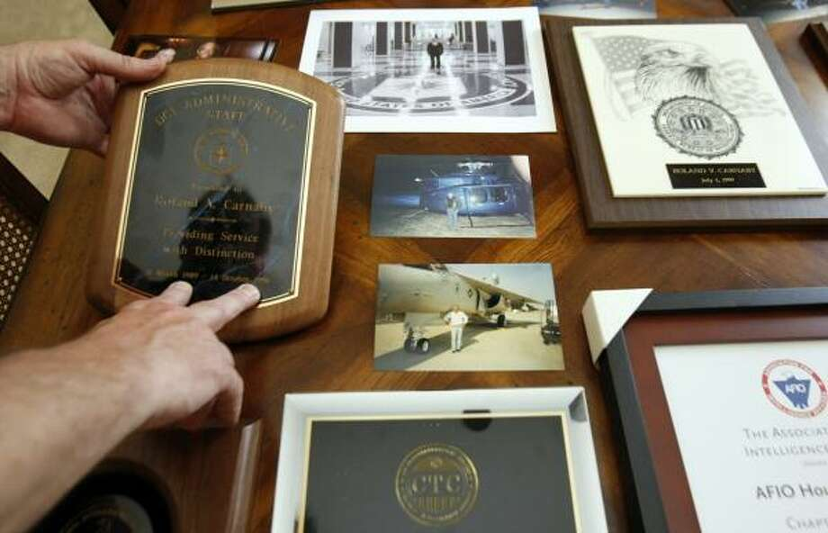 Rob Kouts shows some of the photos, plaques and certificates his brother-in-law displayed. Photo: JOHNNY HANSON, CHRONICLE