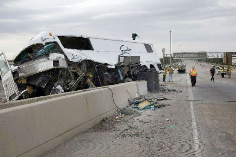 The band bus carrying Grammy-winning Tejano singer Emilio Navaira sits atop a concrete barrier after the March 23 accident that seriously injured Navaira on West Loop 610 at the Southwest Freeway. Photo: Johnny Hanson, Chronicle