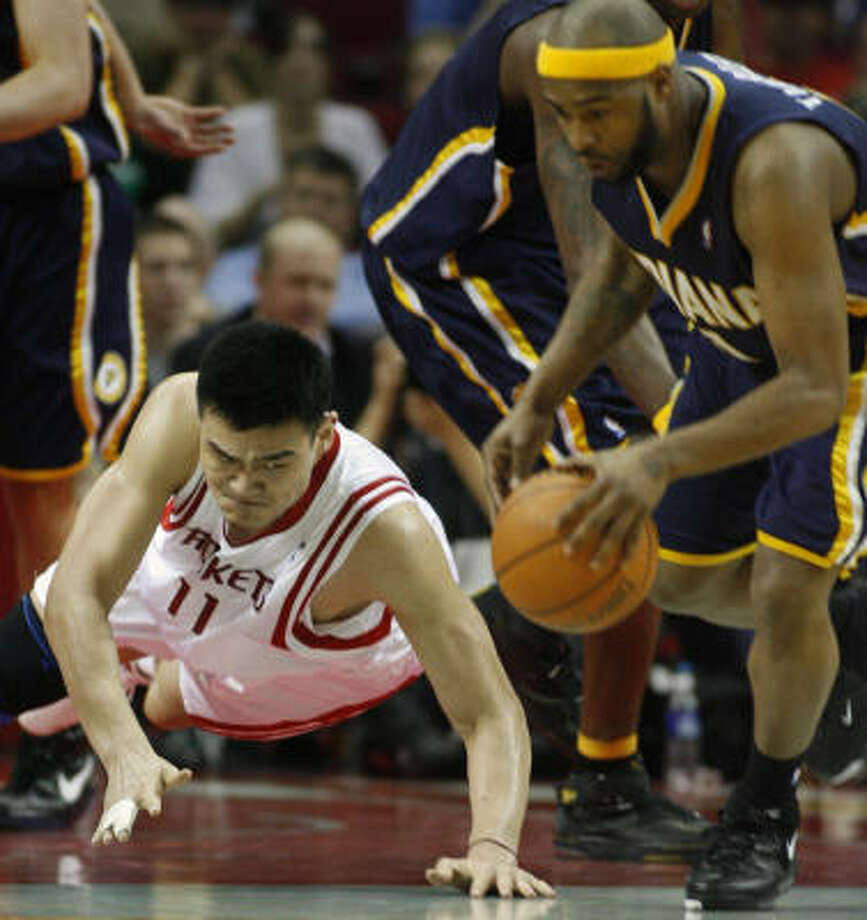 Yao Ming hits the floor but can't beat Jamaal Tinsley to the ball. Photo: Kevin Fujii, Chronicle