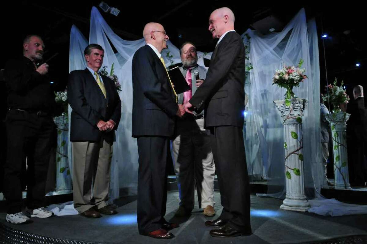 Edward Delph, left, and Peter Schroeter, right, listen as the Rev. Jim Larson, center, at their wedding ceremony at Rocks on Sunday July 24, 2011 in Albany, NY. They have been together since the 1970's. State Senator Neil Breslin is a witness, at left. Sunday was the first day that marriages for the state's new same sex marriage law could be performed. Senator Breslin voted in favor of the law. ( Philip Kamrass / Times Union)