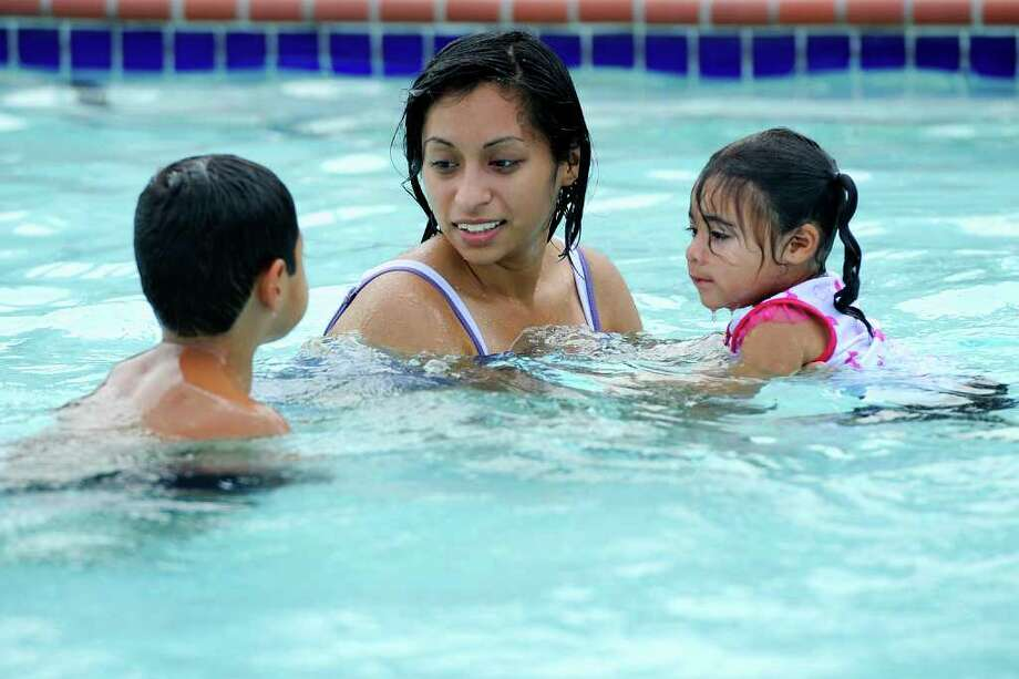 Veronica Varela, center, of Beaumont, her son Alex, 7, left, and 2-year-old daughter, Violet, enjoy the cool waters at Alice Keith Park pool on Saturday afternoon. While the Midwest to the Northeast is in the grip of a record-breaking heat wave with temperatures toping the 100-degree range, Beaumont has remained in the mid-90s. Valentino Mauricio/The Enterprise