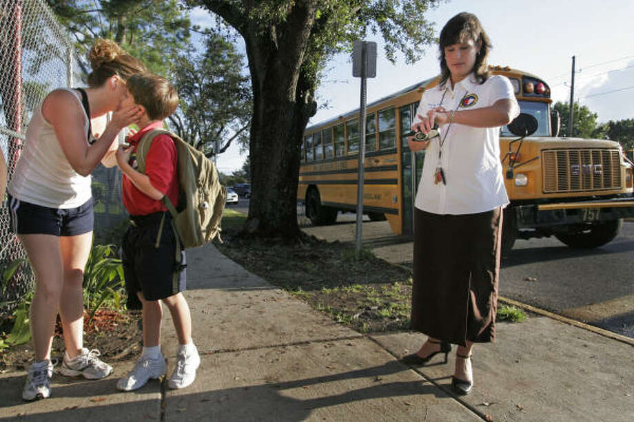Principal Anna Faye Marciante checks her watch as Stephanie Gilmore gives her son, Bert, 8, a kiss after dropping him at Alice Harte Elementary charter school in New Orleans. Photo: ALEX BRANDON, AP
