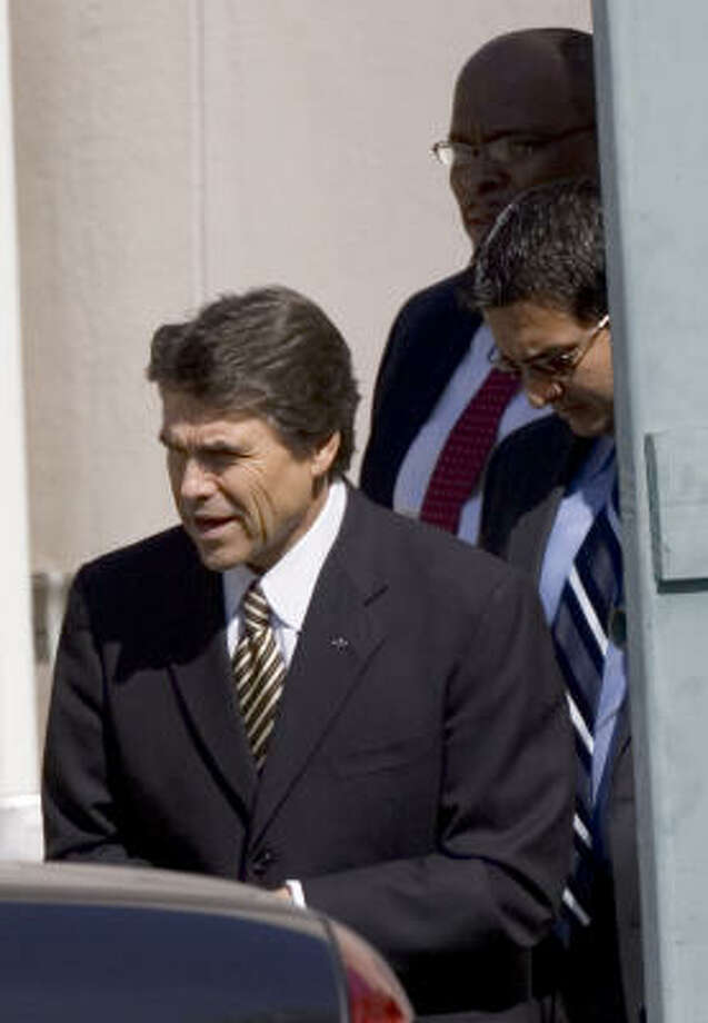 Gov. Rick Perry leaves a meeting with African-American ministers at a Houston hotel Thursday. Photo: BRETT COOMER, CHRONICLE