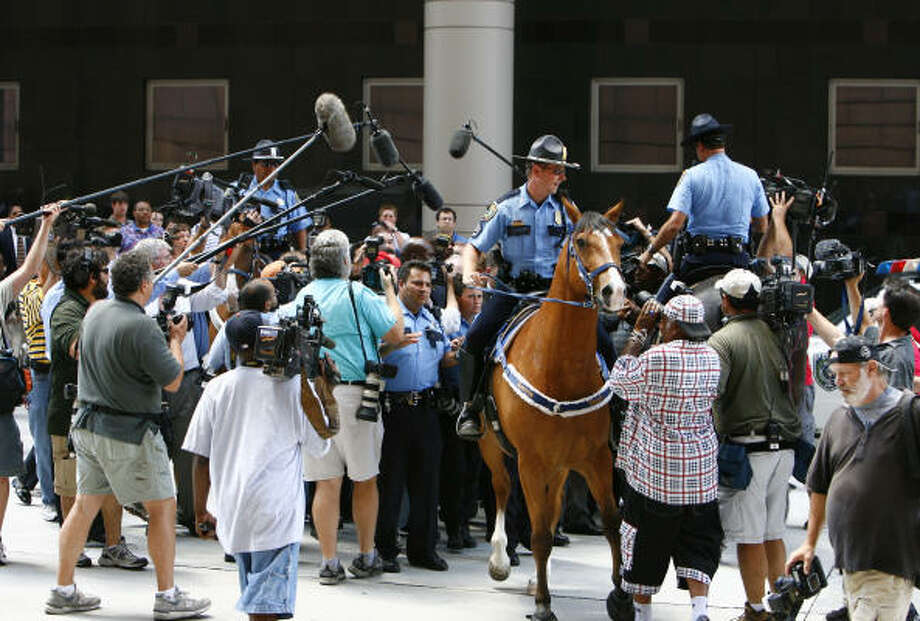 A swarm of media tries to get a photo or quote from Ken Lay. Photo: Nick De La Torre, CHRONICLE