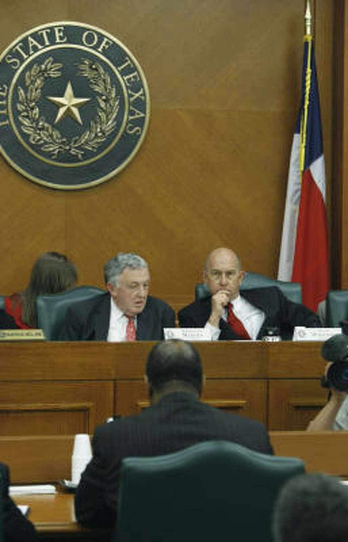 Ed Owens, foreground, interim executive director of the Texas Youth Commission, speaks during a committee meeting on March 8 in Austin. Rep. Jerry Madden, R-Plano, left, and Sen. John Whitmire, D-Houston, listen.