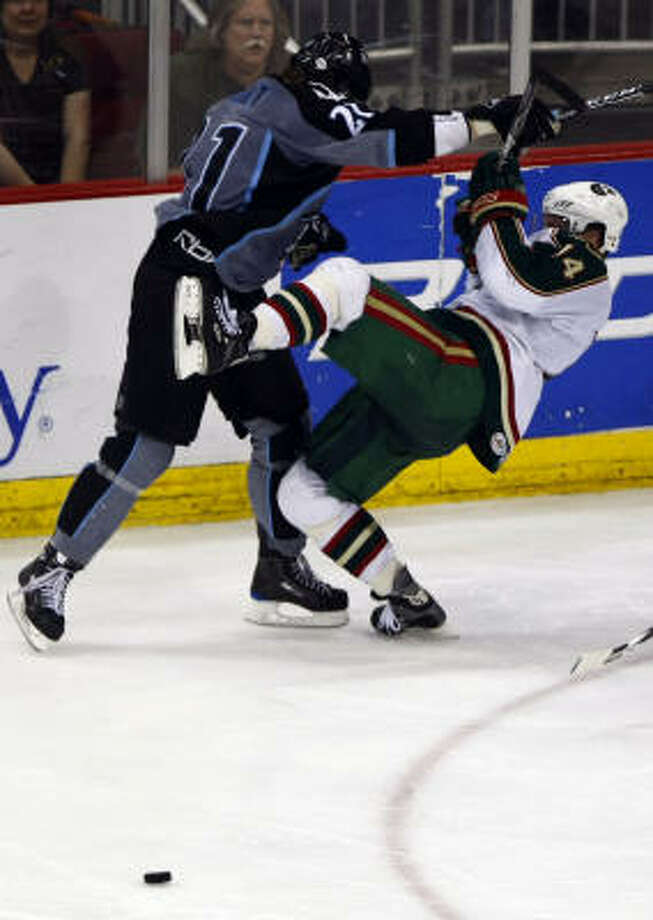 Aeros center Tony Hrkac is knocked to the ice by Milwaukee Admirals winger Triston Grant during the third period. Photo: Smiley N. Pool, Houston Chronicle