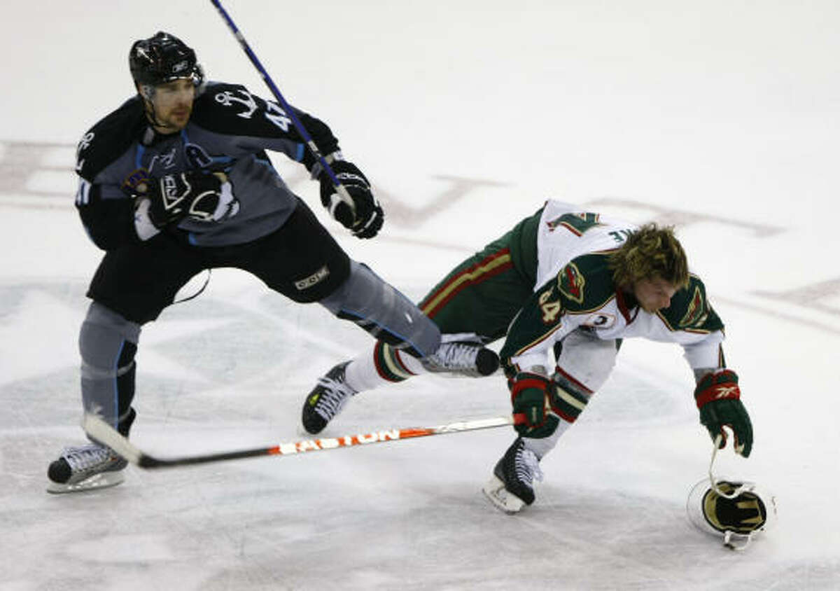 Aeros winger Corey Locke (84) has his helmet knocked off as he is checked by Milwaukee Admirals winger Hugh Jessiman during the third period.