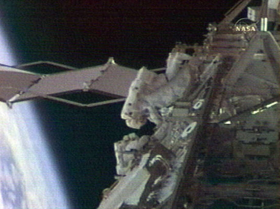 In this image from NASA TV mission specialists Steve Swanson and Pat Forrester are shown as they remove launch restraints on a spacewalk outside the international space station today. Photo: AP