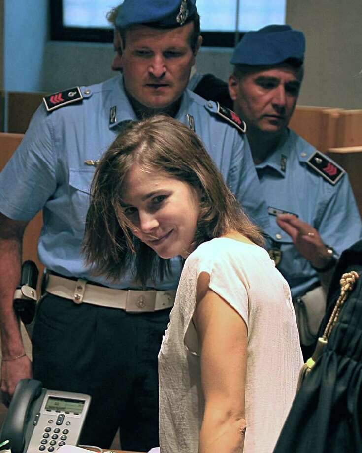 American student Amanda Knox looks at photographers during a hearing in Perugia, Italy on Monday. Independent experts presented the conclusions of their review of the DNA evidence collected against Knox and  her co-defendant Raffaele Sollecito.  DNA evidence played a crucial role in securing the convictions of Amanda and Raffaele Sollecito in the 2007 murder of Meredith Kercher, who was stabbed to death in the apartment she shared with the Seattle exchange student. (AP Photo/Stefano Medici) Photo: Stefano Medici, ASSOCIATED PRESS / AP2011