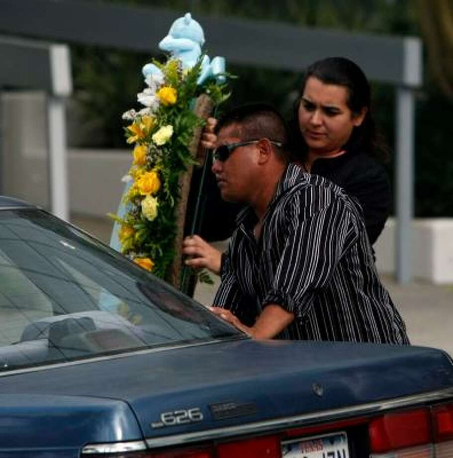 "José Martinez Sr., the father of the child long known as ""Beloved Doe,"" picks up a wreath of flowers from the FBI's Houston office on Thursday. Photo: JOHNNY HANSON, CHRONICLE"