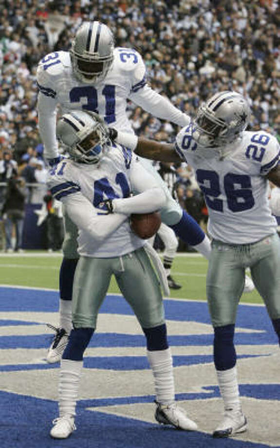 Cowboys cornerback Terence Newman (41), safeties Roy Williams (31) and Ken Hamlin celebrate after Newman returned an interception for a touchdown in the second quarter. Photo: LM Otero, AP