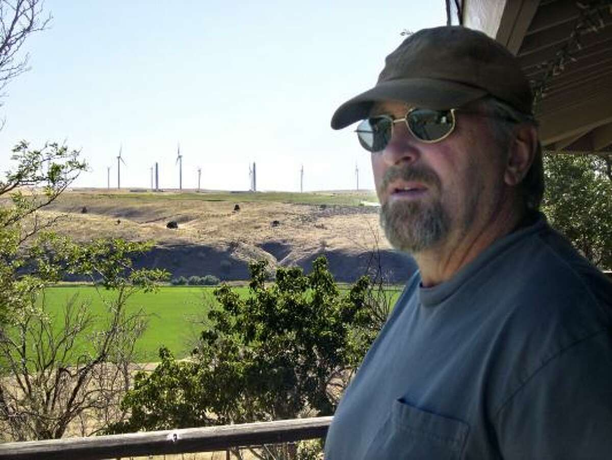 Mike Eaton of Boardman, Ore., now has a view of a wind turbine farm being built near his home. Some researchers say vibrations and low-frequency noise from the turbines can cause health problems.
