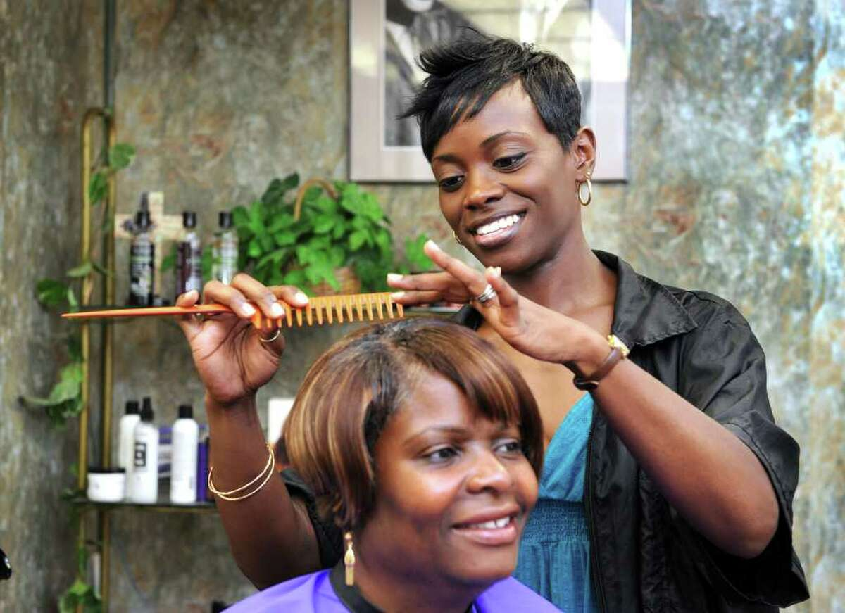 Tanisha Jamison, who, with her husband, T.J., owns A.T.&J's Beauty Salon and Training Center in Danbury, works on Maud MacArthur's hair Thursday. The Jamisons are trained in a technique known as Mindstylz. Photo taken Thursday, July 21, 2011.