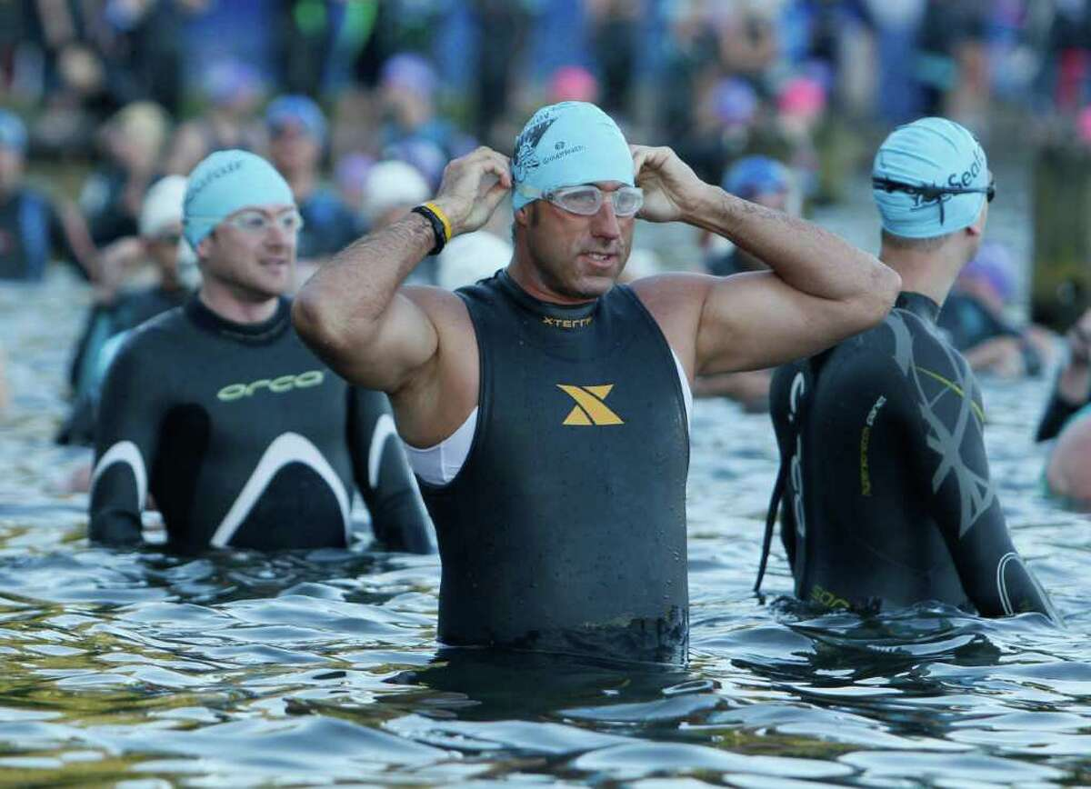 A man Prepares his goggles before starting the Benaroya Research Institute Seafair Triathlon at Seward Park in Seattle on Sunday, July 24, 2011