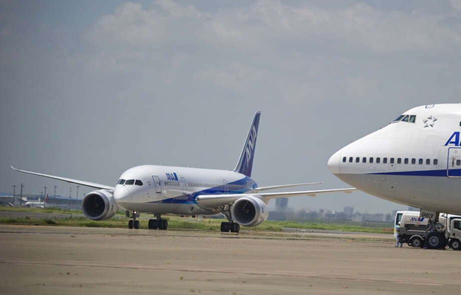 A Boeing flight-test 787 Dreamliner in All Nippon Airways livery (left) taxis near an ANA Boeing 747 in July 2011, during service ready operational validation in Japan. Photo: Boeing