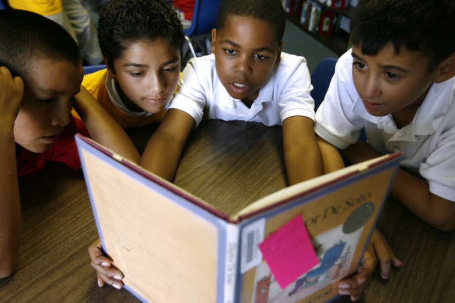 Boys read together at Powell Point Elementary's library. From left are Tony Olalde, 10; Benjamin Ruiz, 12; Johnathan Green, 11, and Matthew Gomez, 9. Photo: Sharon Steinmann, Chronicle