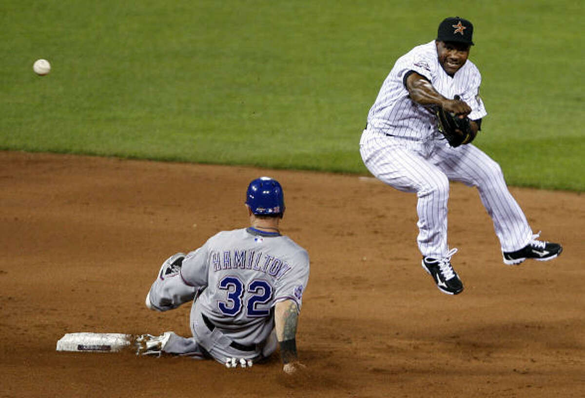 The Astros' Miguel Tejada, right, forces out Josh Hamilton and turns a double play by throwing to first base.