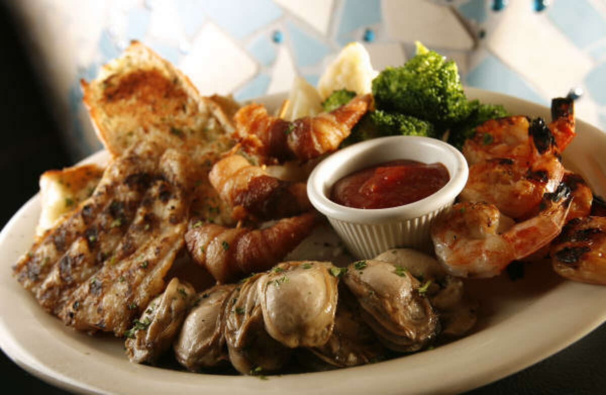 Valentino's grilled seafood platter features grouper topped with scallion-and-garlic butter, pan-grilled oysters and shrimp rolled in bacon.