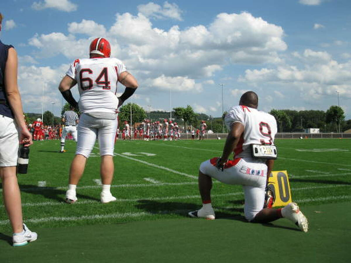 Marburg Mercenaries offensive lineman Tony Chesney, left, and running back Sean Cooper watch play during a German Football Game.