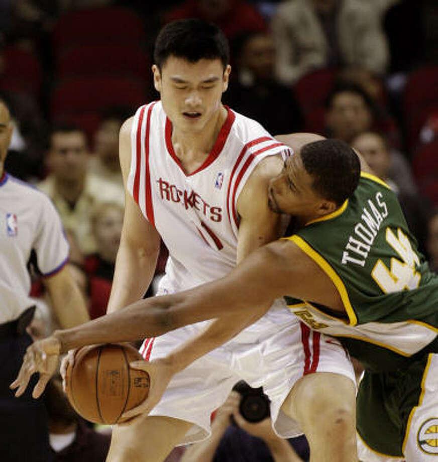 Yao Ming protects the ball from Sonics forward Kurt Thomas. Photo: Dave Einsel, AP