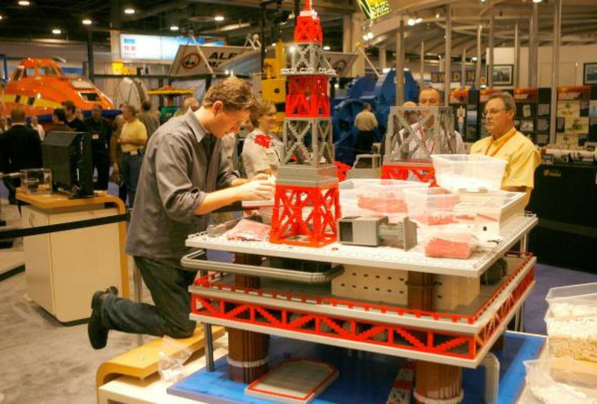 """""""Brick artist"""" Nathan Sawaya works on a scale replica of a drilling platform at Weatherford's booth at the Offshore Technology Conference on Wednesday at Reliant Park."""