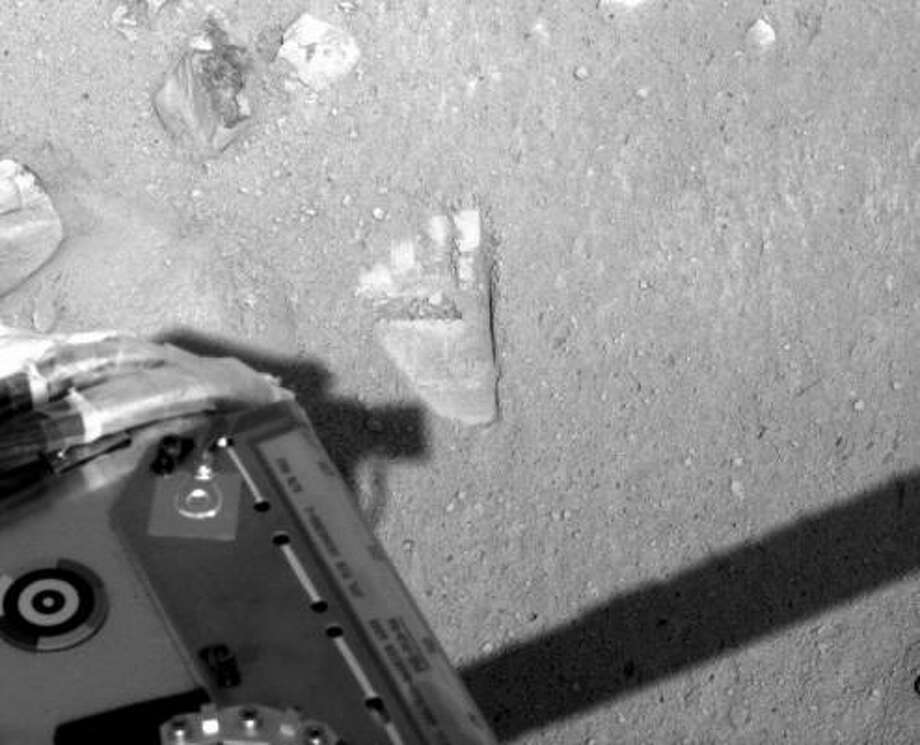 A footprint-like impression on the Mars turf is actually a mark left by the Phoenix lander's robotic arm. Photo: NASA PHOTO