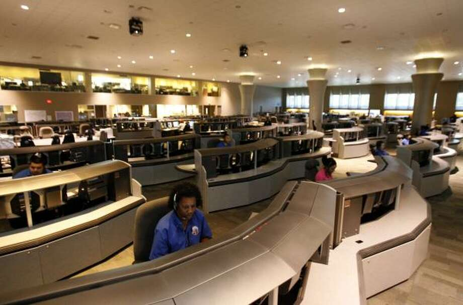 Operators at Houston's emergency call center, such as Marilyn Wright, foreground, take about 9,000 calls a day, and some of them are in a foreign language. The Language Line Services helps translate in those situations. Photo: JOHNNY HANSON, CHRONICLE