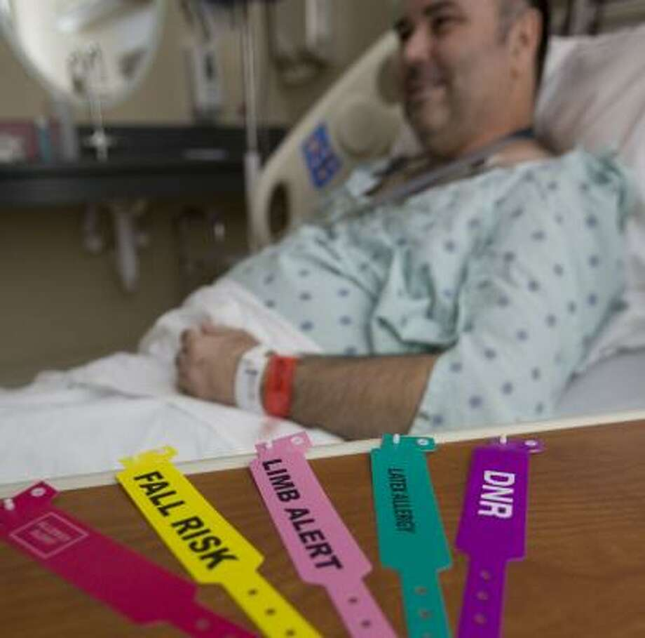James Daniel, a patient at Memorial Hermann-Memorial City Medical Center, wears the current wristband with the new wristbands nearby that the hospital will start using in November. Photo: JAMES NIELSEN, CHRONICLE