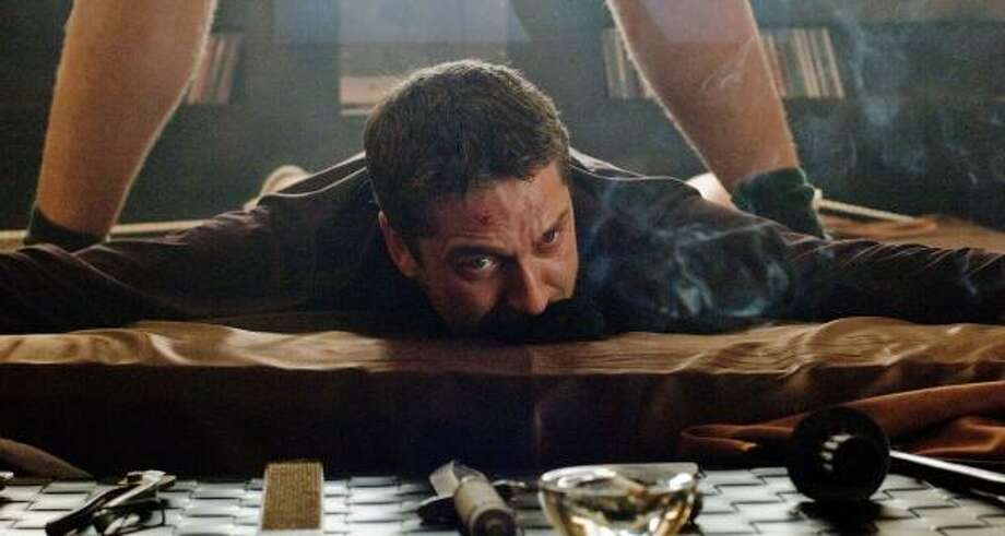 One Two (Gerard Butler) finds himself in a precarious position in RocknRolla. Photo: ALEX BAILEY, WARNER BROS.   ASSOCIATED PRESS