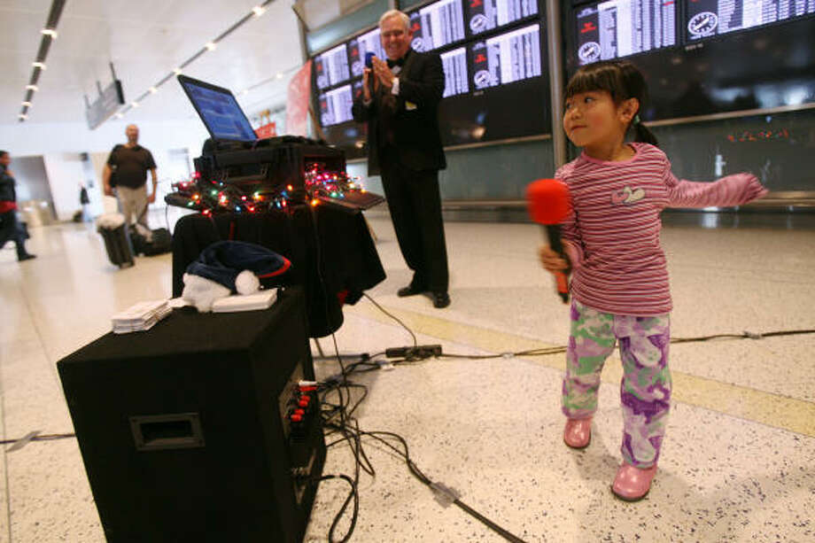 Casandra Ducay, 4, dances as she sings Rudolph the Red-Nose Reindeer at George Bush Intercontinental Airport during the Holiday Karaoke event. Photo: Mayra Beltran, Chronicle