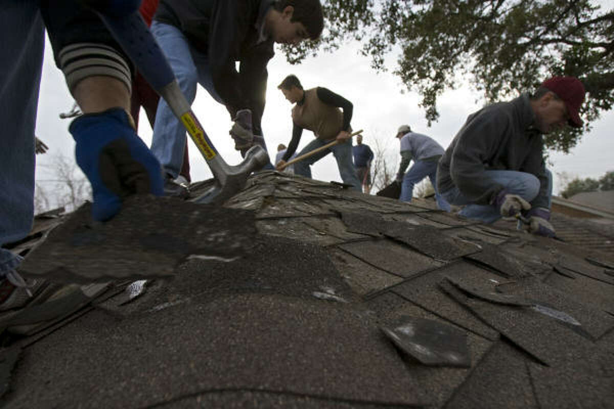 """Volunteers from LINC-Houston, a faith-based nonprofit, repair roof damage caused by Hurricane Ike at Dolores Hedger's home in east Houston in 2009. Hedger applied for FEMA assistance but was turned down because of """"deferred maintenance."""""""