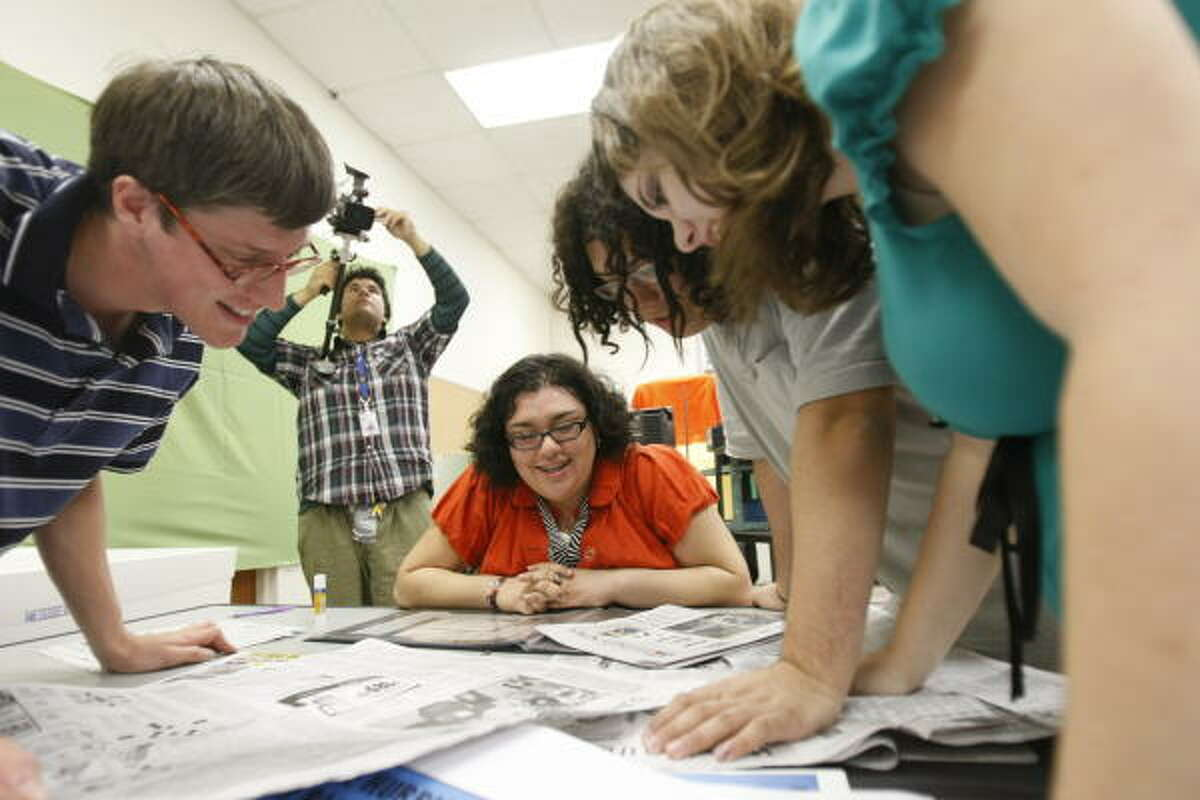Ball High School's Jovanna Torres, 17, center, works with advanced media technology teacher Robert Weiss, far left, and her classmates, from left, William Gomez, 18, Austin Almanza, 17, and Jennifer Willcut, 18, as they look over newspaper clippings.