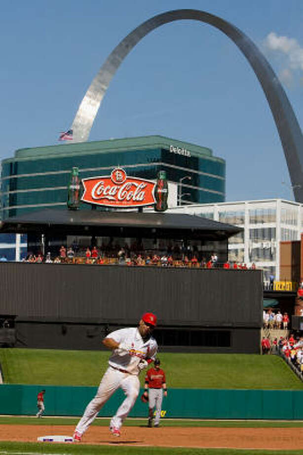 Albert Pujols rounds the bases with the Gateway Arch in the background. Photo: Dilip Vishwanat, Getty Images