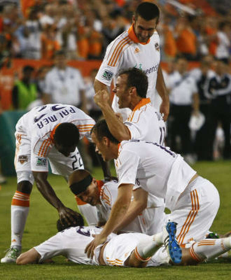 Dynamo midfielder Brad Davis pumps a fist as teammates dog-pile on defender Hunter Freeman after Freeman's goal in the 86th minute. Photo: Michael Paulsen, Chronicle