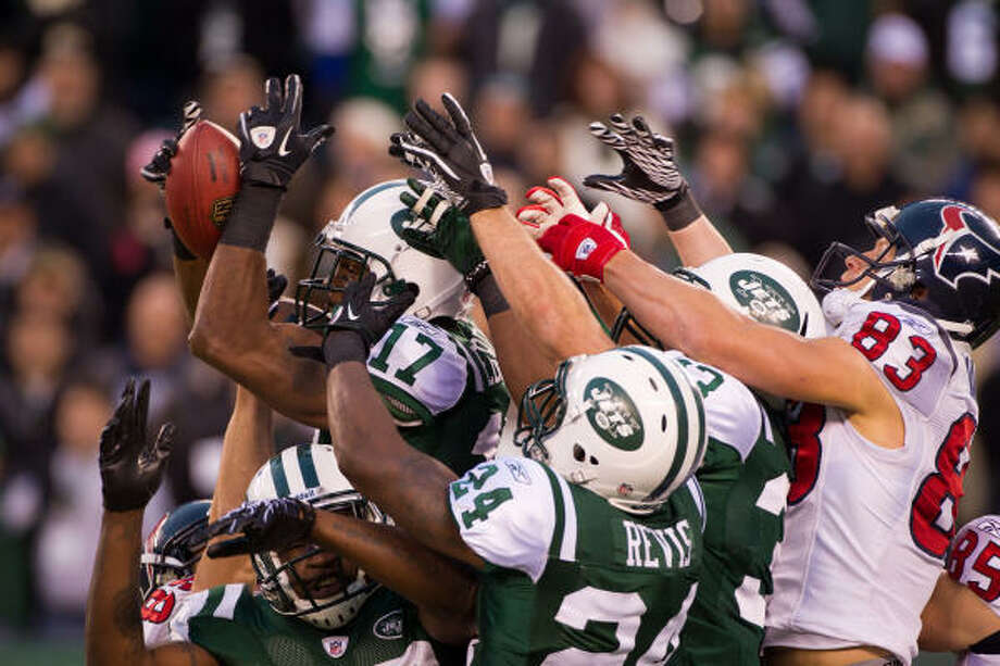 A week after the Texans lost on a last-second Hail Mary pass, their attempt to complete one of their own failed when Jets wide receiver Braylon Edwards (17) outjumped a crowd of players to haul in Matt Schaub's final heave Sunday. Photo: Smiley N. Pool, Chronicle