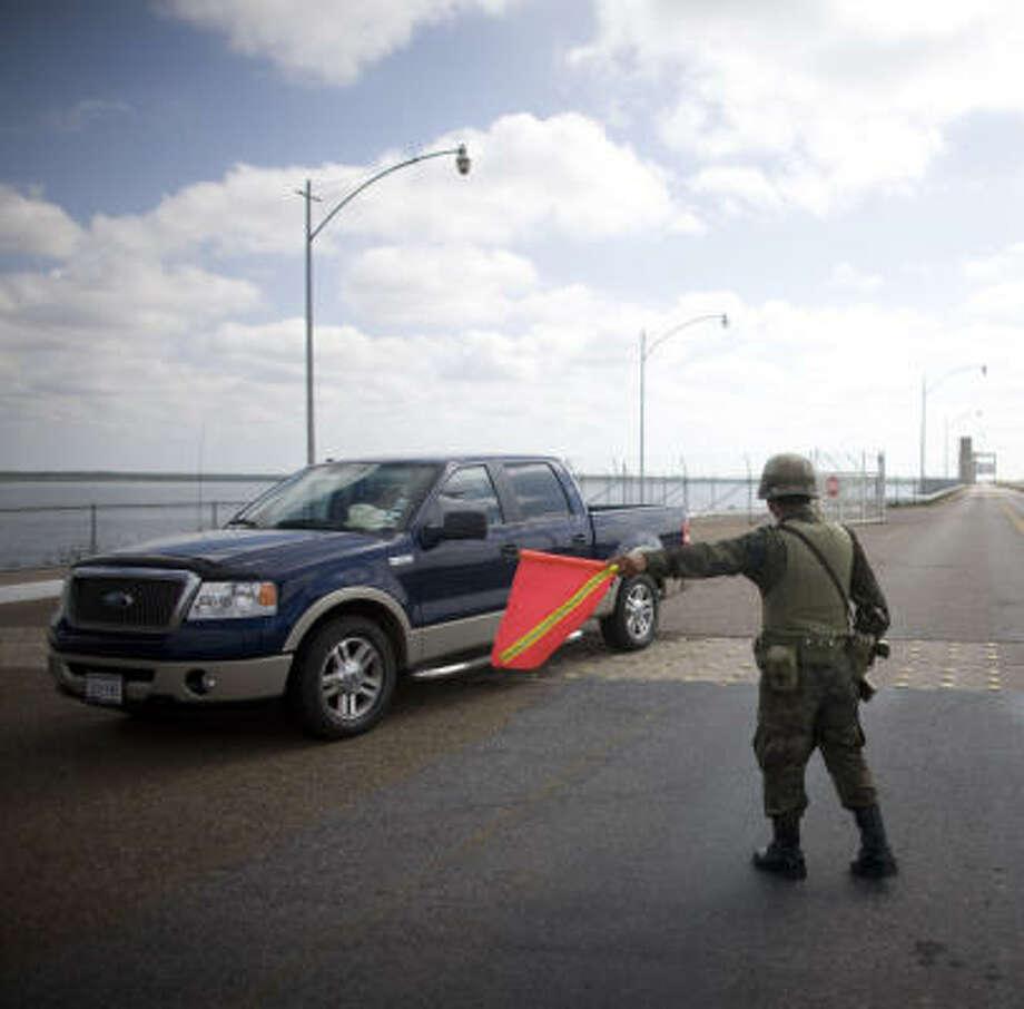 A Mexican soldier signals to a car to be checked at the border near Nueva Ciudad Guerrero, Mexico. Photo: Alexandre Meneghini, AP