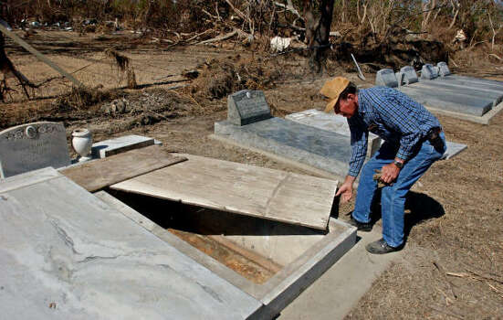 Boyd Nunez, 76, replaces the wooden cover on his father's grave in Oak Grove, La., on Oct. 27, 2005. His father's coffin was moved 300 yards by Hurricane Rita's storm surge. Photo: MARK M. HANCOCK, BEAUMONT ENTERPRISE FILE