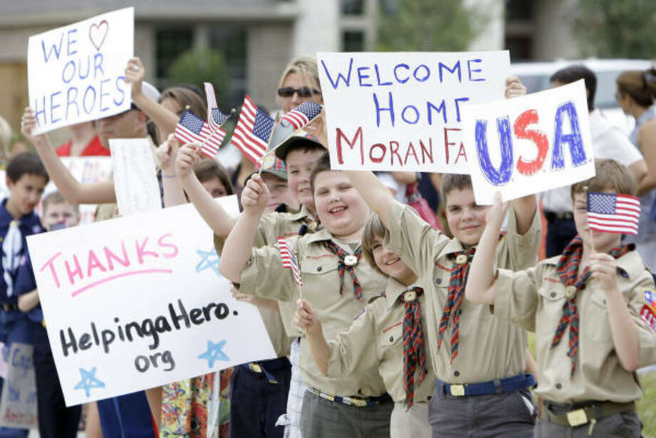 Boy Scouts hold signs and wave flags outside the new home of Retired Capt. Daniel Moran and his family as they wait for the arrival of Secretary of Defense Robert Gates. Photo: Melissa Phillip, Chronicle