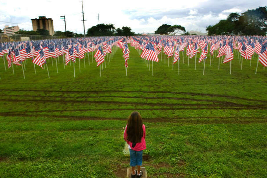 "Alyssah Ruff, 9, of Pearl Harbor, Hawaii stands near the edge of the ""Healing Field"", a memorial of 2,500 flags over-looking the Arizona Memorial during the commemoration marking the 66th anniversary of the Pearl Harbor attack. Photo: Lucy Pemoni, Getty Images"