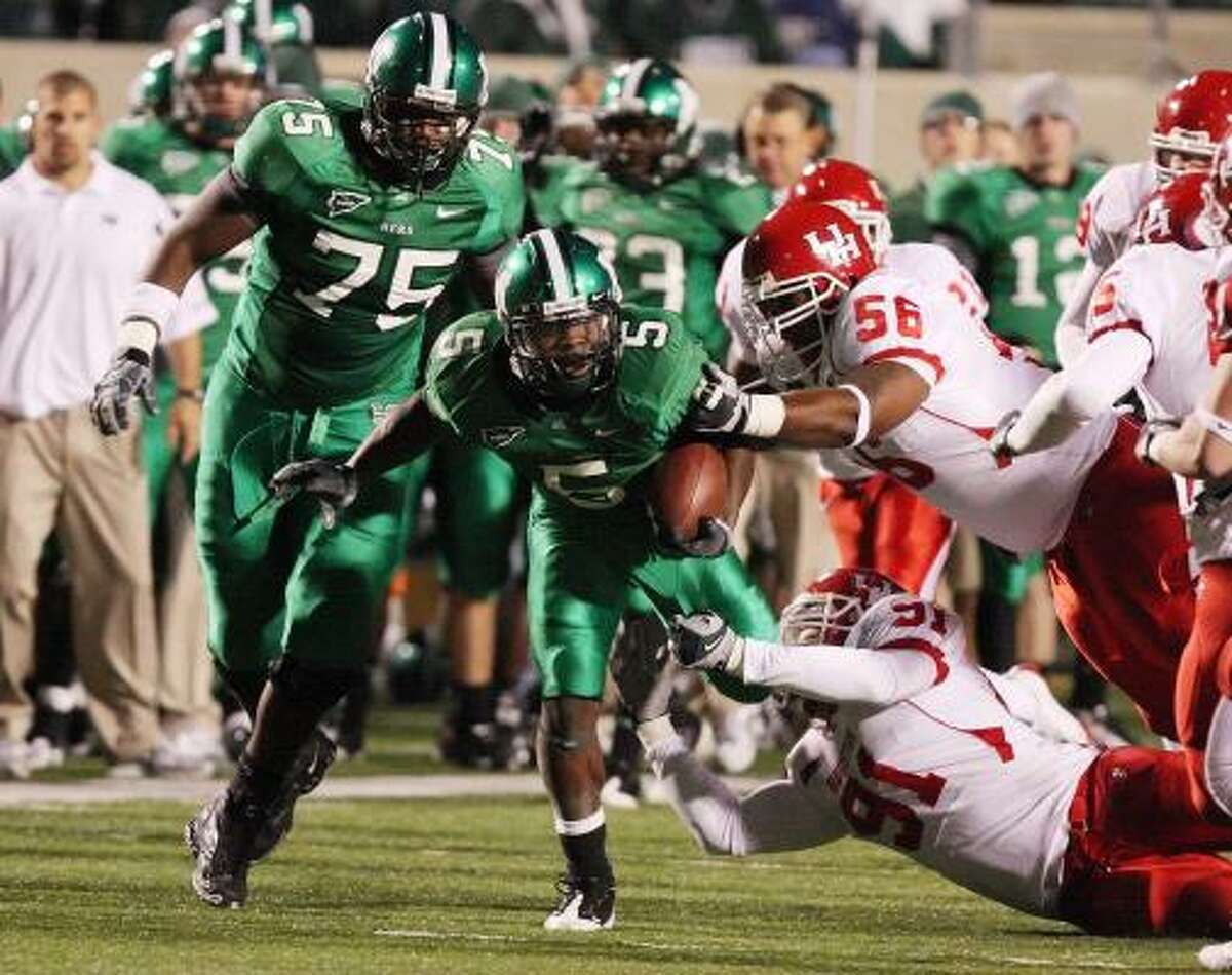Marshall running back Darius Marshall drags UH defenders Cody Pree (56) and Tate Stewart (91) during the Cougars' 37-23 loss.