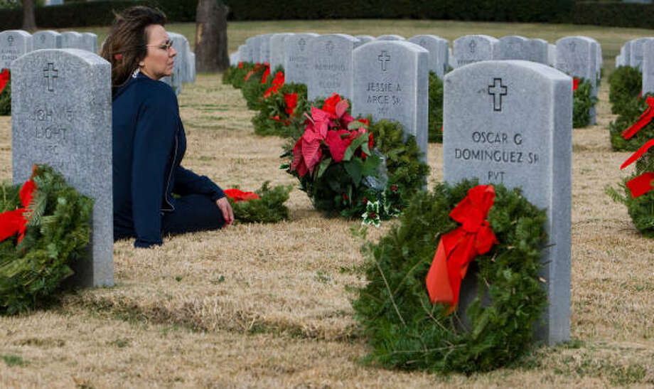 Maggie Juarez, sits by the gravestone of her father, Jesse Arce, after the Wreaths Across America ceremony Saturday at Houston National Cemetery. Photo: Nick De La Torre, CHRONICLE