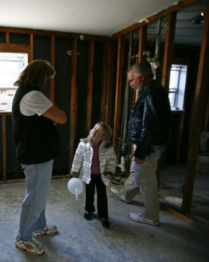Alison and Scott Putman, shown with their 4-year-old, Lindsey, want to rebuild their Kemah home, but their insurance offer won't cover costs of new elevation requirements and other rules. Photo: MICHAEL PAULSEN, CHRONICLE