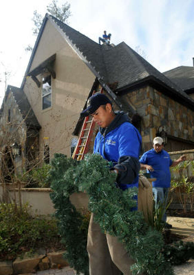 A crew from The Perfect Light, including Jose Gomez, left, and Jesse Hernandez, both of The Woodlands, install Christmas lights at a home in the Player Manor subdivision of Sterling Ridge. Photo: Jerry Baker, For The Chronicle