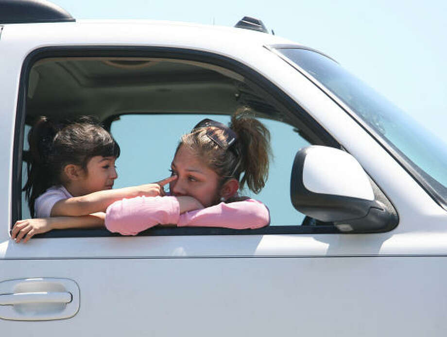 Nia (left) and mother Lila Rodriguez wait on the shoulder of the road as the searchers work near Beltway 8 on Tuesday. Photo: Mayra Beltran, Chronicle