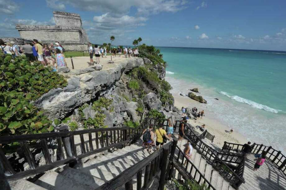 Tourists visit the Pre-Columbian Mayan site of Tulum, built on the eastern coast of the Yucatan Peninsula on the Caribbean Sea, in the Mexican state of Quintana Roo, on December 3, 2010. This coastal archaeological site is one of the most well-preserved of the Mayan civilization. Photo: CRIS BOURONCLE, AFP/Getty Images / 2010 AFP